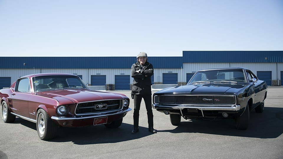 Ep2 - Brian Johnson standing with the '68 Dodge Charger & rival '67 Ford Mustang Fastback at the Atlanta Motorsports Park Track.